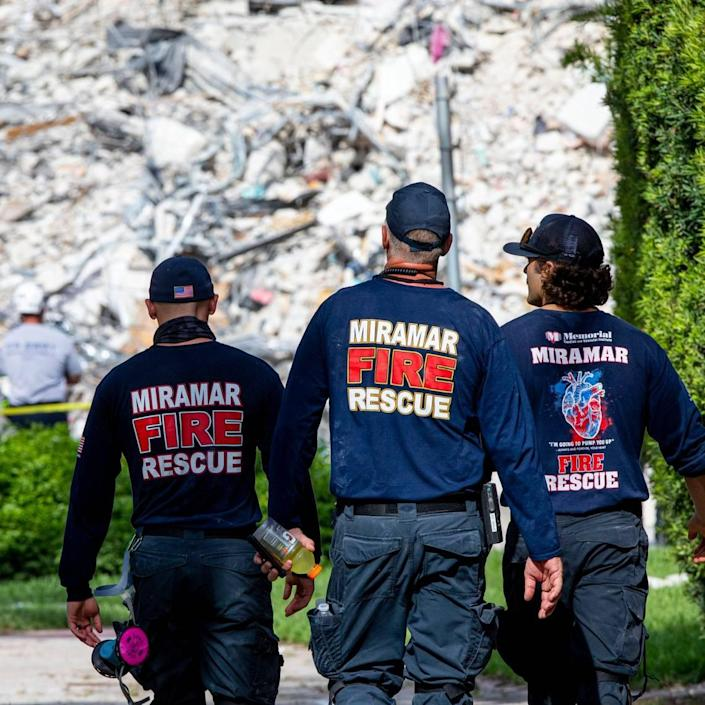 First responders from Miramar walk toward the rubble of the Champlain Towers South collapse, one day after a shift from search and rescue to recovery, in Surfside, Florida, on Thursday, July 8, 2021.