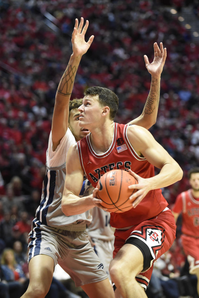 San Diego State forward Yanni Wetzell, right, drives past the defense of Nevada forward Johncarlos Reyes (12) during the first half of an NCAA college basketball game Saturday, Jan. 18, 2020, in San Diego. (AP Photo/Denis Poroy)