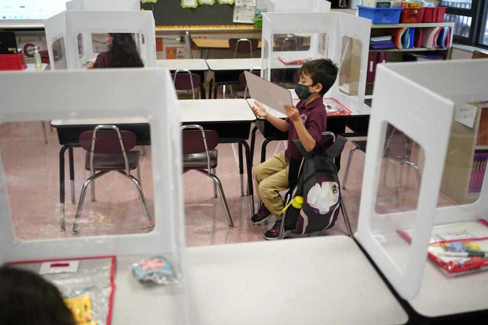 Third graders do their work behind see-though partitions at Christa McAuliffe School in Jersey City, N.J., Thursday, April 29, 2021. Kindergarten through third grade students are returning to their school buildings in Jersey City for their first time in over a year. New Jersey's two largest cities have begun making their return to classrooms in person after working remotely because of the COVID-19 outbreak. Students in Jersey City began returning to school today, just days after Newark officials said they were expanding in-person instruction to four days a week, up from two. (AP Photo/Seth Wenig)