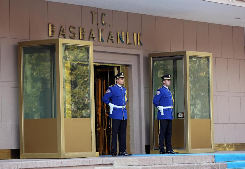 Two police offices stand at the entrance of Turkish Prime Minister Recep Tayyip Erdogan's office shortly after police subdued a man who was carrying a fake bomb in Ankara, Turkey, Thursday, Nov. 21. 2013. Police fired two warning shots in the air before overpowering and arresting him, said an aide to the prime minister. The 53-year-old man, identified as Tugrul B., was carrying a device made to look like a bomb, the official said. He was being questioned and the motive for his action was not immediately known.(AP Photo/Burhan Ozbilici) (AP Photo/Burhan Ozbilici)