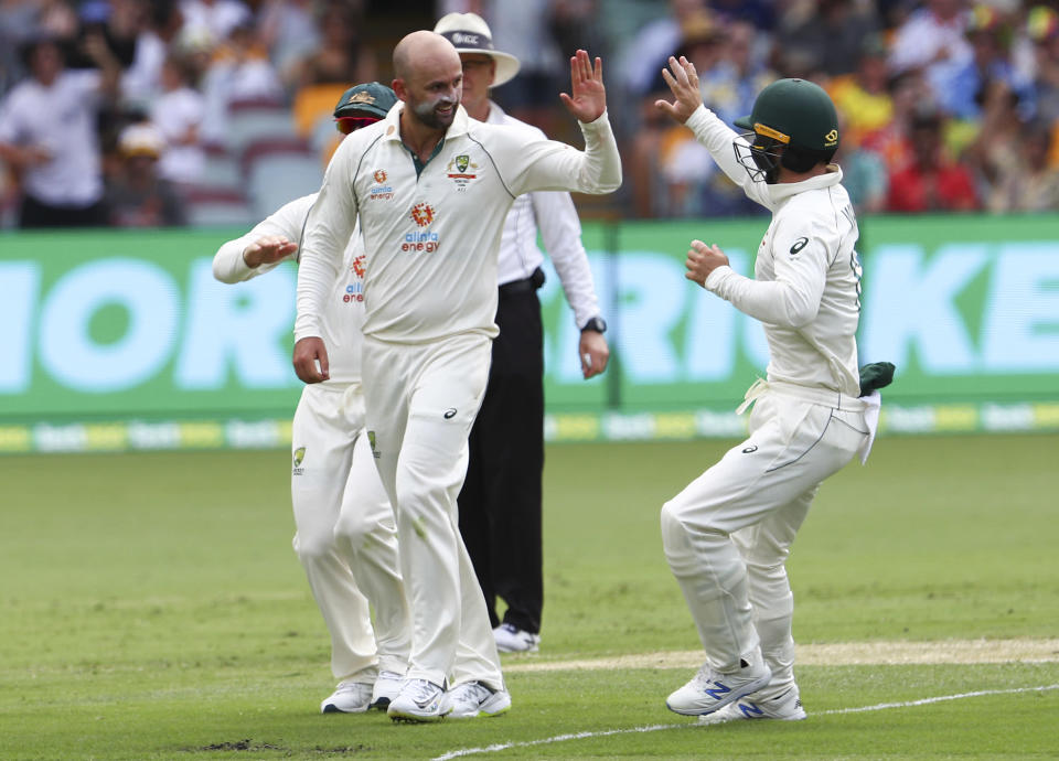 Australia's Nathan Lyon, left, is congratulated by teammate Matthew Wade after taking the wicket of India's Rohit Sharma during play on day two of the fourth cricket test between India and Australia at the Gabba, Brisbane, Australia, Saturday, Jan. 16, 2021. (AP Photo/Tertius Pickard)