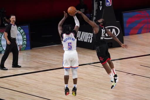 Oklahoma City Thunder's Luguentz Dort (5) has his 3-point attempt blocked by Houston Rockets' James Harden (13) as referee Pat Fraher, left rear, looks on during the second half of an NBA first-round playoff basketball game in Lake Buena Vista, Fla., Wednesday, Sept. 2, 2020. (AP Photo/Mark J. Terrill)