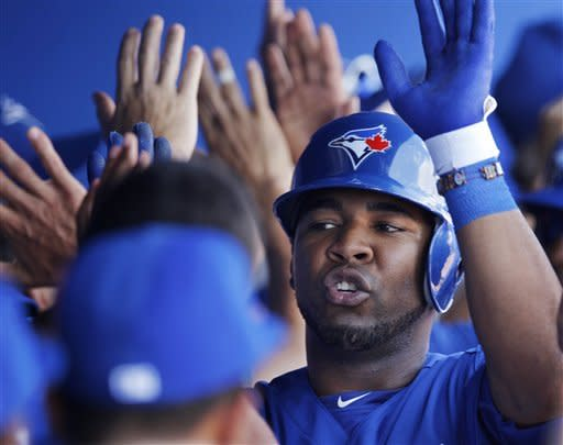 Teammates greet Toronto Blue Jays designated hitter Edwin Encarnacion in the dugout after he hit a three-run home run off New York Yankees relief pitcher Manuel Banuelos during their spring training baseball game in Dunedin, Fla., Wednesday, March 14, 2012. (AP Photo/Kathy Willens)