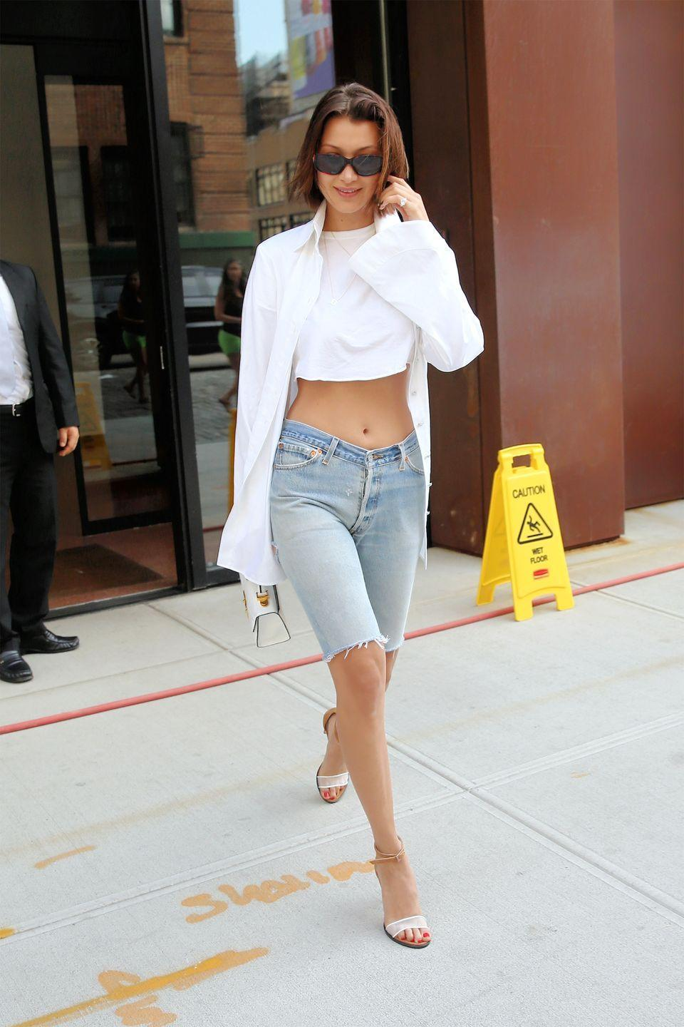<p>In a Kreist white shirt as a jacket, crop top, Dear Frances sandals and jorts leaving Gigi's apartment in NYC.</p>