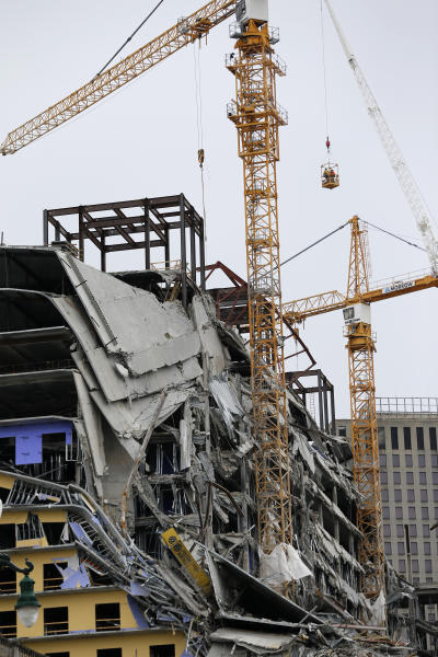 Workers in a bucket hoisted by a crane begin the process of preparing the two unstable cranes for implosion at the collapse site of the Hard Rock Hotel, which underwent a partial, major collapse while under construction last Sat., Oct., 12, in New Orleans, Friday, Oct. 18, 2019. Authorities plan to blow up the two towering construction cranes that have become unstable at the site of the collapsed hotel. They hope to bring down the cranes with series of small controlled blasts just ahead of approaching tropical weather. The mayor has imposed a state of emergency to seize property and force people out if necessary. They hope to avoid more damage to gas and power lines and historic buildings. (AP Photo/Gerald Herbert)