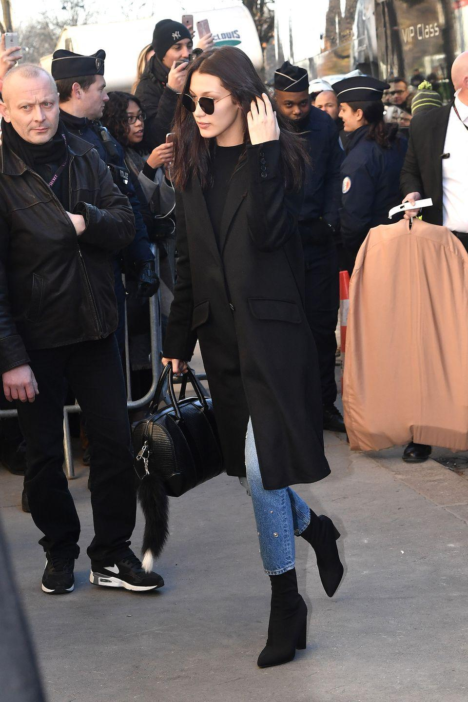 <p>In a black peacoat, black top, studded light wash jeans, black sock boots, a leather handbag and cat eyed sunglasses. </p>