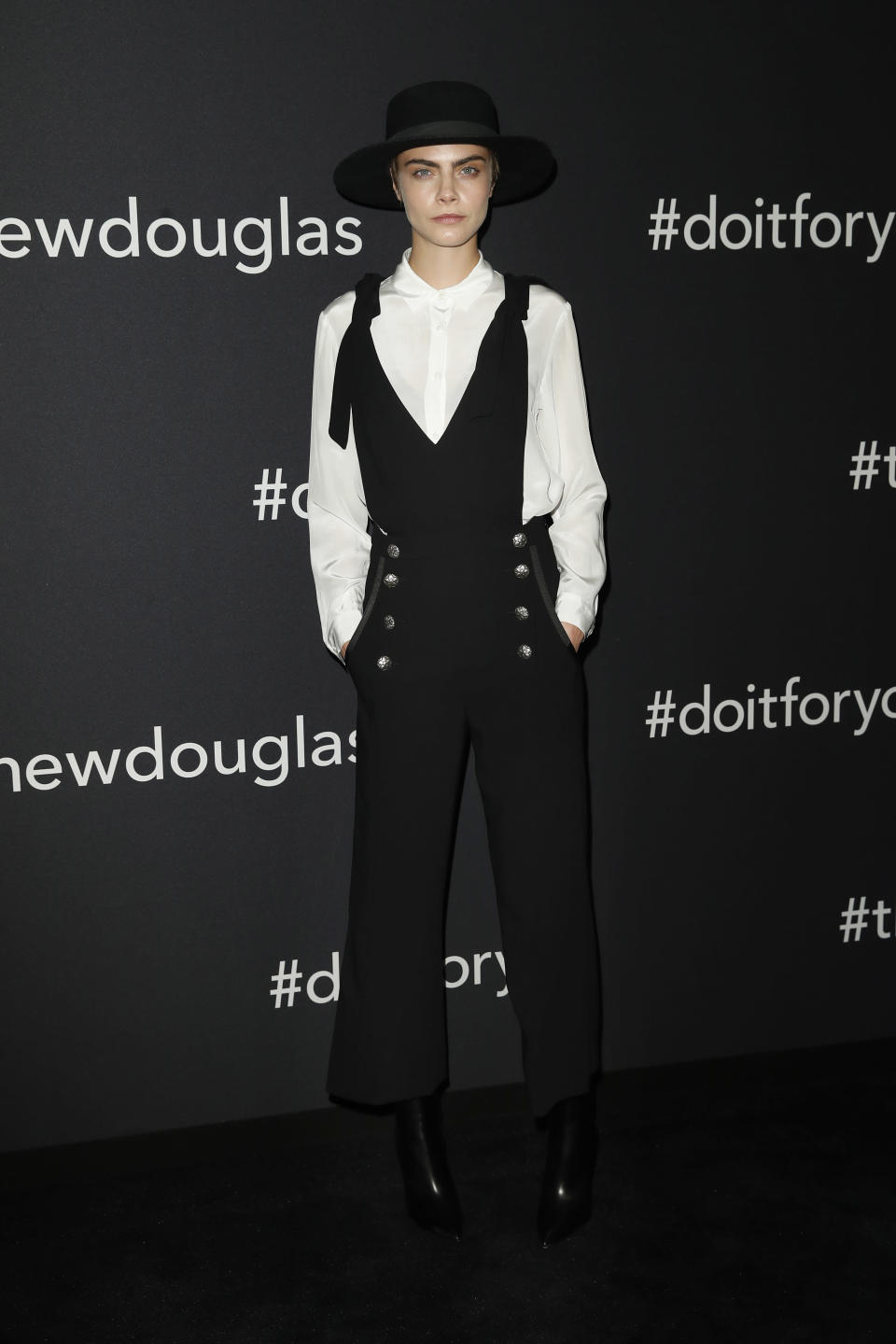 <p>On May 30, Cara Delevigne attended the Douglas X Peter Lindbergh campaign launch in Berlin wearing a black jumpsuit and co-ordinating hat. <em>[Photo: Getty]</em> </p>