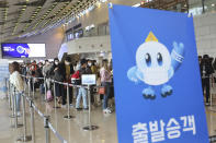 """Passengers wearing face masks to help protect against the spread of the coronavirus line up to board planes ahead of the upcoming Chuseok holiday, the Korean version of Thanksgiving Day, at the domestic flight terminal of Gimpo airport in Seoul, South Korea, Wednesday, Sept. 30, 2020. The signs read: """"Departure passenger."""" (AP Photo/Ahn Young-joon)"""