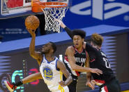 Golden State Warriors forward Andrew Wiggins (22) drives to the basket between Portland Trail Blazers guard Anfernee Simons (1) and center Jusuf Nurkic (27) during the first half of an NBA basketball game in San Francisco, Friday, Jan. 1, 2021. (AP Photo/Tony Avelar)