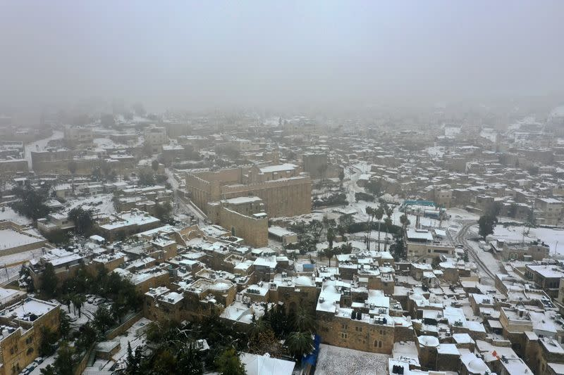 A picture taken with a drone shows roofs of buildings and houses covered with snow following snowfall in Hebron in the Israeli-occupied West Bank