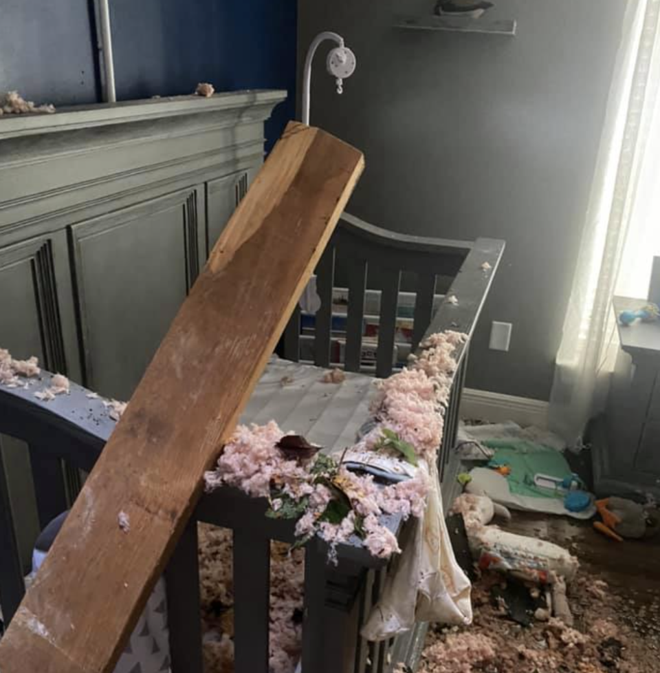 The bedroom of a baby boy damaged by a tree.