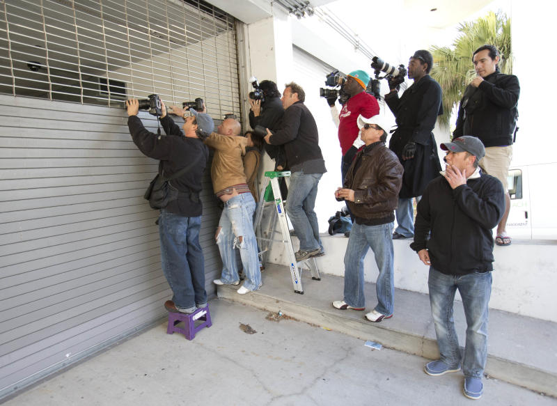 Photographers jockey for position as they wait for police to transport pop singer Justin Bieber, Thursday, Jan. 23, 2014 in Miami Beach, Fla. Police have Bieber and R&B singer known as Khalil for alleged drag-racing on a Miami Beach street. (AP Photo/Wilfredo Lee)