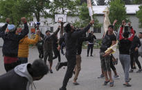 Players celebrate after winning a game of cricket in Blazuj migrant camp in Bosnia's capital of Sarajevo Wednesday, May 19, 2021. Thanks to a Rome-based humanitarian group, migrants stranded at camps in Bosnia were able to forget their everyday difficulties and enjoy cricket. The Baobab Experience group has brought cricket equipment for the migrants in the Bosnian capital of Sarajevo and the central town of Tuzla, offering a rare opportunity for relaxation and fun for the people who spend months, if not years, stuck in camps while fleeing war and poverty in their nations and chasing their dreams of a better future. (AP Photo/Kemal Softic)