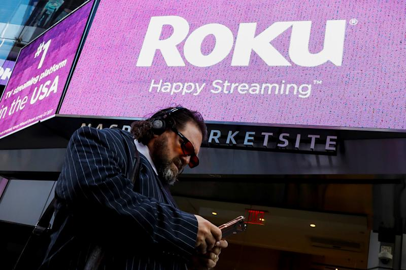 A man passes by a video sign display with the logo for Roku Inc, a Fox-backed video streaming firm, after the company's IPO at the Nasdaq Marketsite in New York, U.S., September 28, 2017. REUTERS/Brendan McDermid