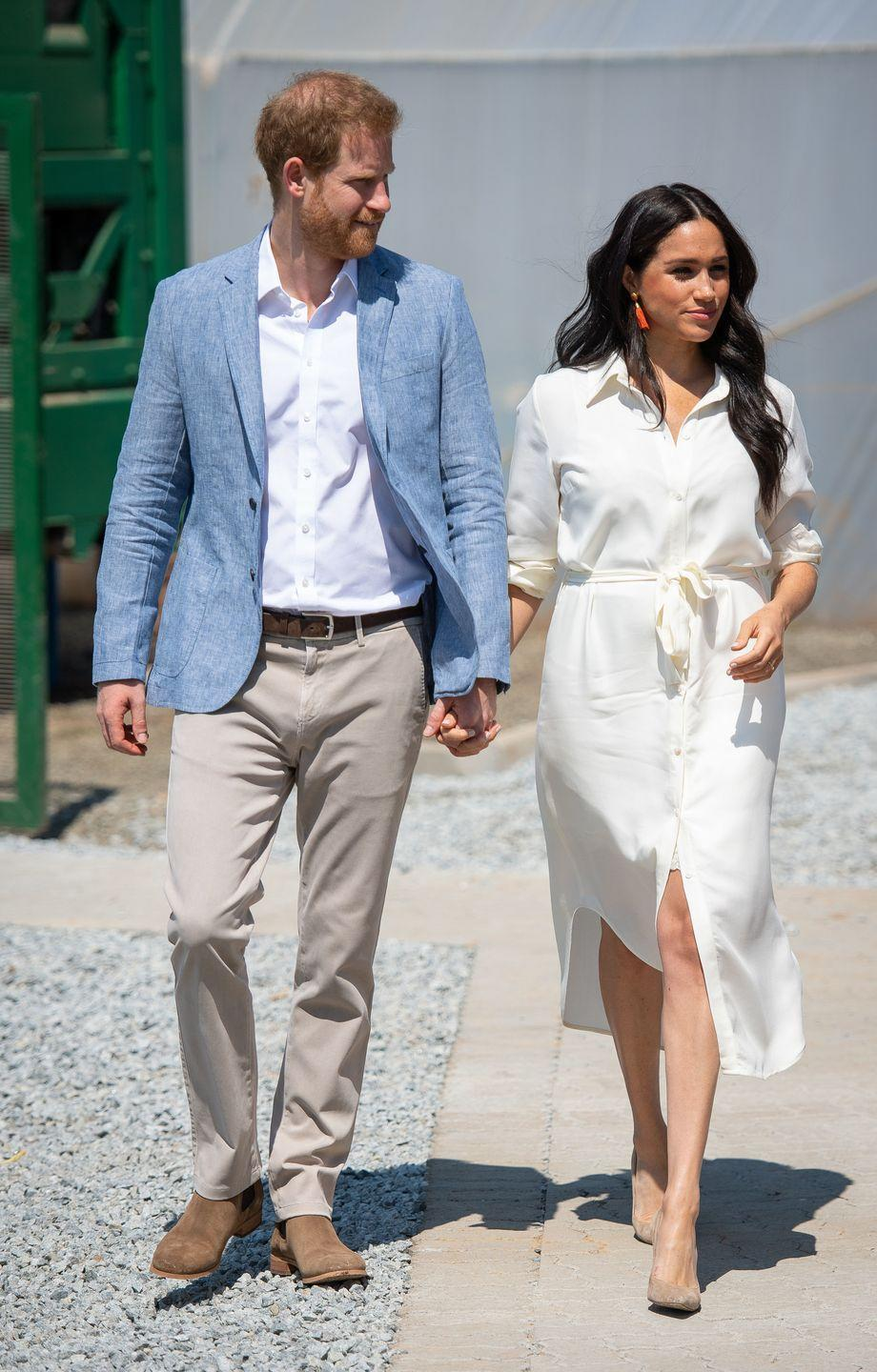 "<p>The Duke and Duchess of Sussex continued their royal tour with a visit to Tembisa township outside Johannesburg. <a href=""https://www.townandcountrymag.com/style/fashion-trends/a29300614/meghan-markle-white-dress-pink-earrings-johannesburg/"" rel=""nofollow noopener"" target=""_blank"" data-ylk=""slk:Meghan wore a white shirt dress"" class=""link rapid-noclick-resp"">Meghan wore a white shirt dress</a> for the event, paired with bright pink earrings and nude heels. </p>"