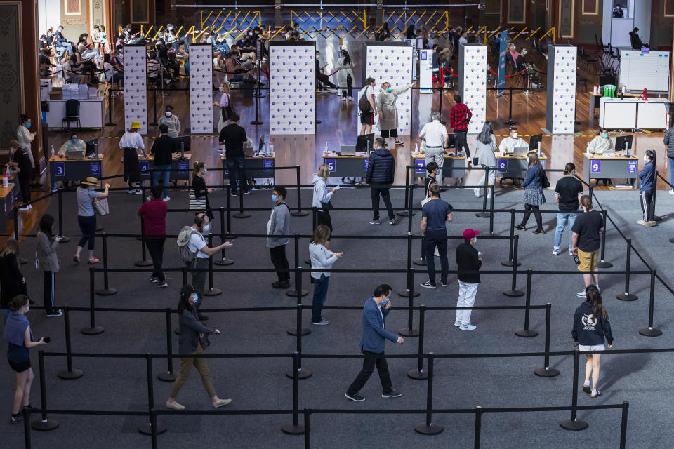 People queue up inside the Royal Exhibition Building COVID19 Vaccination Hub in Melbourne, Thursday. Source: AAP