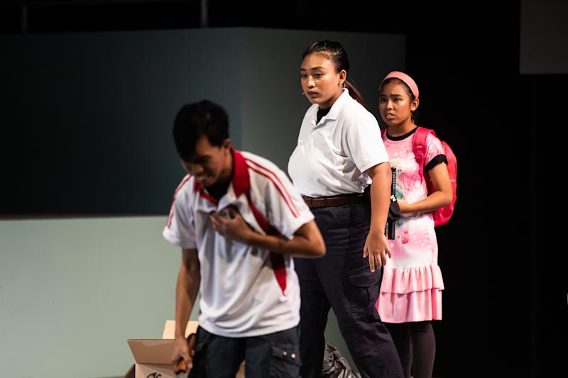 Zakia Fathiha Zaharul Hendrey, 17, (middle), as a policewoman in the play. (PHOTO: ArtsWok Collaborative)