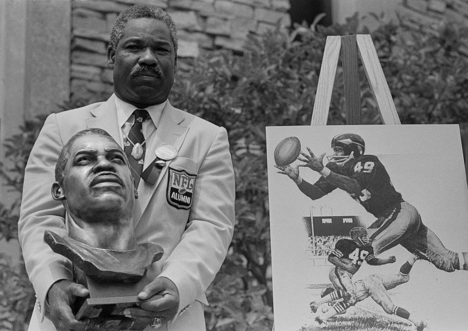 Former Cleveland Browns and Washington Redskins halfback and wide receiver Bobby Mitchell poses with his bronze bust after being inducted into the Pro Football Hall of Fame in ceremonies in Canton, Ohio, July 30, 1983.  (AP Photo/Gus Chan)