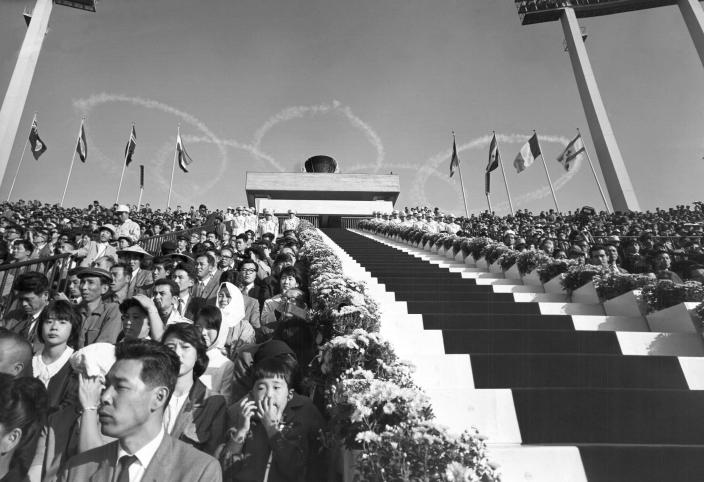 FILE - In this Oct. 10, 1964, file photo, five interlocking Olympic rings are thrown high in the sky by jet planes drift over the stadium during the opening ceremonies for the 1964 Olympics at the National Stadium in Tokyo. The famous 1964 Tokyo Olympics highlighted Japan's resiliency. It was a prospering country that was showing off bullet trains, transistor radios, and a restored reputation just 19 years after devastating defeat in World War II. Now Japan and Tokyo are on display again, attempting to stage the postponed 2020 Tokyo Olympics in the midst of a once-in-a century pandemic. (AP Photo, File)