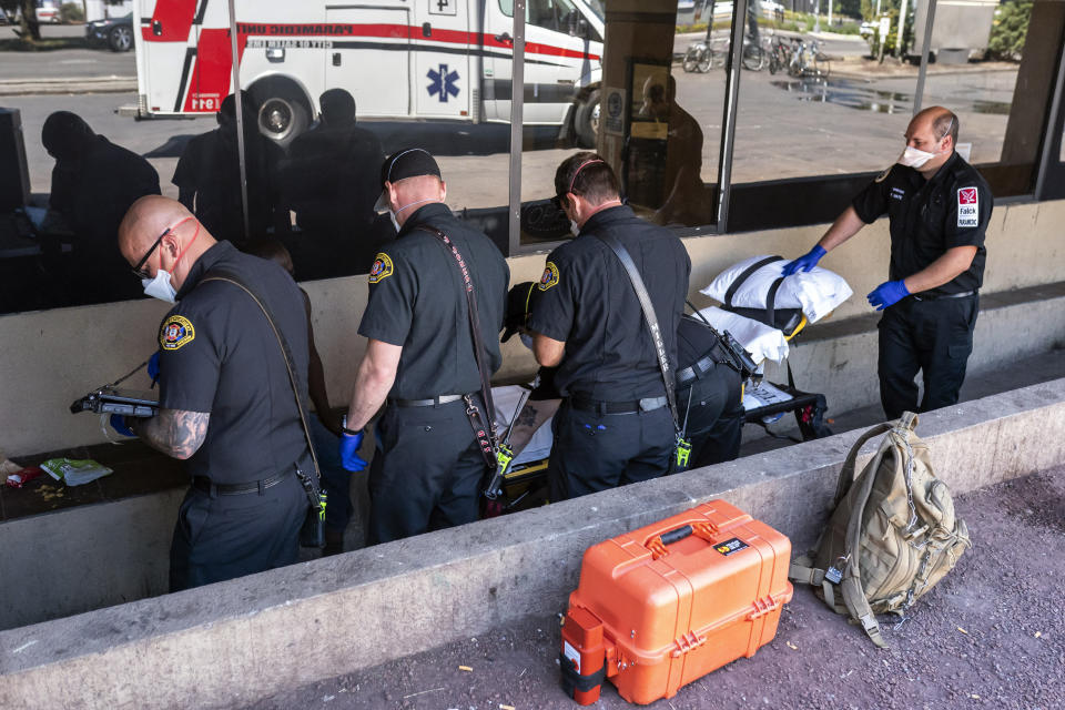 Salem Fire Department paramedics and employees of Falck Northwest ambulance service respond to a heat exposure call during a heat wave, Saturday, June 26, 2021, in Salem, Ore. (AP Photo/Nathan Howard)