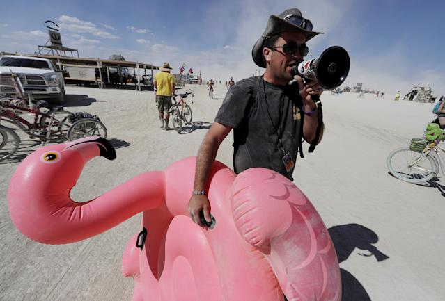 "<p>Burning Man participant Joshua ""Kanizzle"" Cunningham of Burning Man Information Radio gives a running commentary with a megaphone on people's costumes or lack thereof as approximately 70,000 people from all over the world gathered for the 1st full day of the annual Burning Man arts and music festival in the Black Rock Desert of Nevada, Aug. 28, 2017. (Photo: Jim Bourg/Reuters) </p>"
