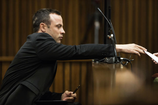 Oscar Pistorius passes a note for his legal counsel from the dock on the fourth day of his trial at the high court in Pretoria, South Africa, Thursday, March 6, 2014. Pistorius is charged with murder for the shooting death of his girlfriend Reeva Steenkamp on Valentine's Day in 2013. (AP Photo/Marco Longari, Pool)