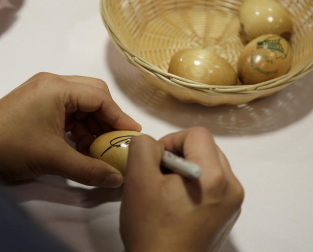 Julian Castro, former U.S. Secretary of Housing and Urban Development and candidate for the 2020 Democratic presidential nomination, signs wooden eggs before speaking at Saint Anselm College, Wednesday, Jan. 16, 2019, in Manchester, N.H. (AP Photo/Mary Schwalm)