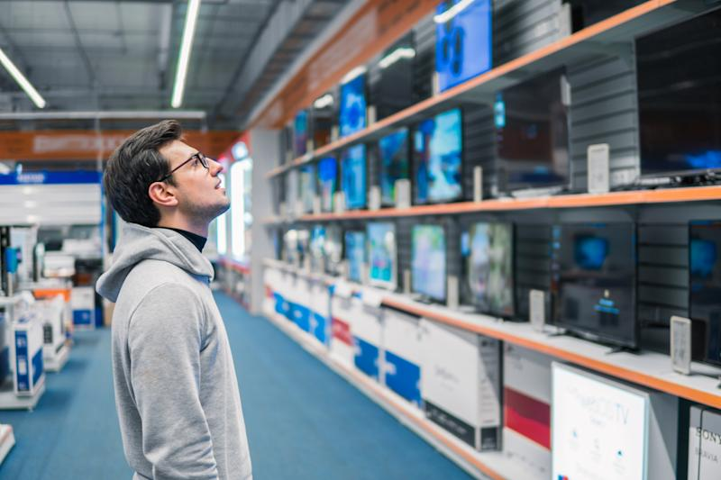 Smart modern male customer choosing large TV-sets at electronics store. He looks wondered. New screen generations.