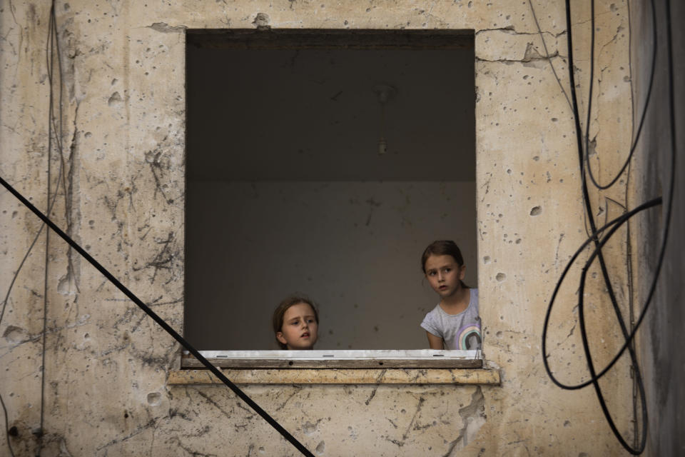 Arina Klochkov, 7, right, and her sister Zoya visit their damaged home after last week it was hit by a rocket fired from the Gaza Strip, in Petah Tikva, central Israel, Friday, May 21, 2021. A cease-fire took effect early Friday after 11 days of heavy fighting between Israel and Gaza's militant Hamas rulers that was ignited by protests and clashes in Jerusalem. (AP Photo/Oded Balilty)
