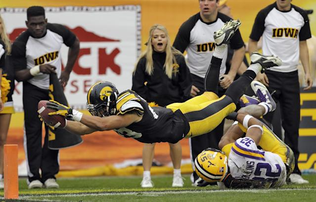 Iowa wide receiver Jordan Cotton (23) dives for the end zone after getting tripped up by LSU cornerback Jalen Collins (32) on a kickoff return during the fourth quarter of the Outback Bowl NCAA college football game Wednesday, Jan. 1, 2014, in Tampa, Fla. Officials ruled Cotton went out-of-bounds on the 4-yard line. LSU won the game 21-14. (AP Photo/Chris O'Meara)