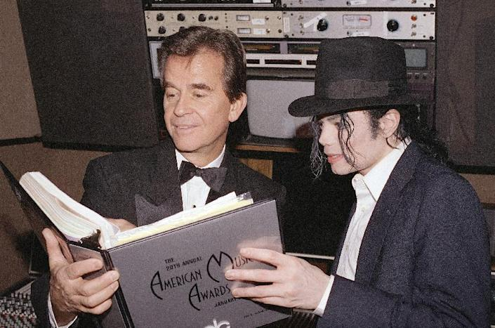 """FILE - In this Jan. 24, 1993 file photo, singer Michael Jackson and American Music Awards executive producer Dick Clark go over the script during rehearsals for The American Music Awards at the Shrine Auditorium in Los Angeles. Clark, the television host who helped bring rock `n' roll into the mainstream on """"American Bandstand,"""" died Wednesday, April 18, 2012 of a heart attack. He was 82. (AP Photo/file)"""