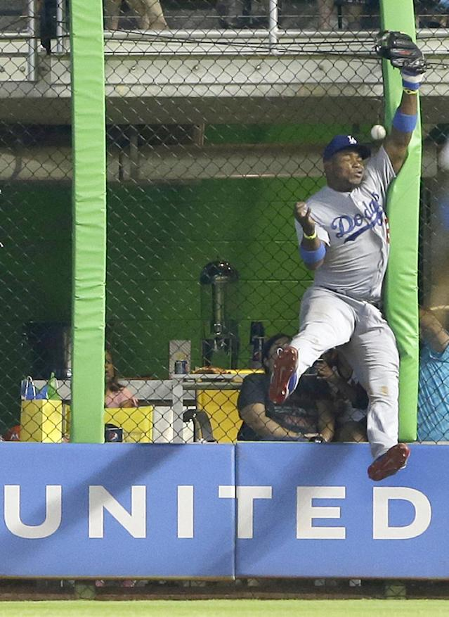 Los Angeles Dodgers right fielder Yasiel Puig is unable to catch a ball at the fence hit by Miami Marlins' Jeff Baker for a double, during the ninth inning of a baseball game, Sunday, May 4, 2014 in Miami. Puig retreated and made a leaping try for an acrobatic catch but slammed against the fence, and the ball deflected off it and hit him in the face. Puig collapsed to his stomach and was slow to rise, and he walked off the field with an arm around a trainer. Adeiny Hechavarria scored on the play as the Marlins defeated the Dodgers 5-4. (AP Photo/Wilfredo Lee)