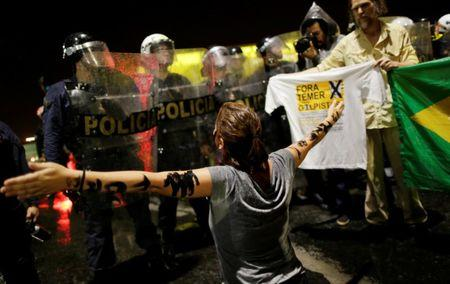 A demonstrator reacts near riot police officers during a protest against Brazil's President Michel Temer in front of the Planalto Palace in Brasilia, Brazil, May 18, 2017.  REUTERS/Ueslei Marcelino