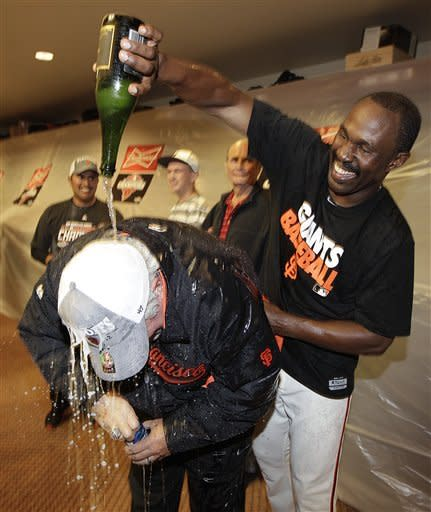 San Francisco Giants general manager Brian Sabean, wearing cap, is covered with champagne by special assistant Shawon Dunston celebrate after defeating the San Diego Padres to win the National League West Division title after a baseball game, Saturday, Sept 22, 2012, in San Francisco. (AP Photo/Ben Margot, Pool)