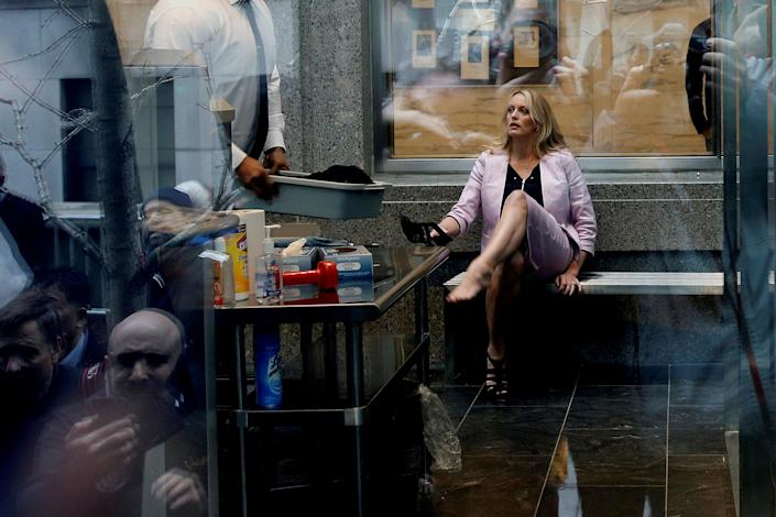 Stormy Daniels puts her shoes back on after passing through a security screening at federal court in April. (Photo: Shannon Stapleton/Reuters)