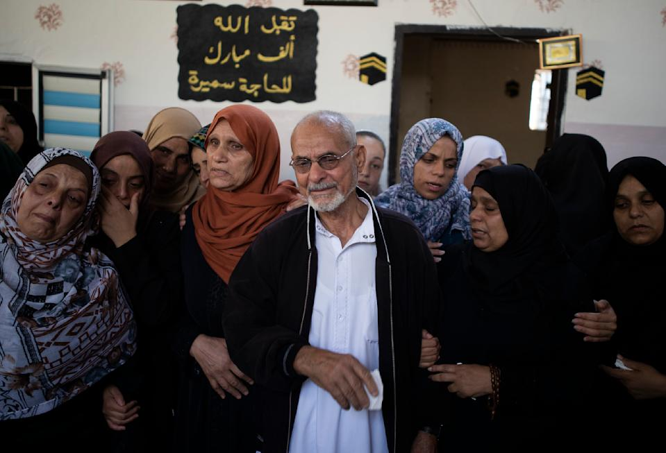 Relatives mourn the death of Palestinian Hamas militant, Mohammad Abu Namous, 27, in the family home during his funeral in the Jabaliya refugee camp, northern Gaza Strip, Sunday, Aug. 18, 2019. Gaza's Health Ministry said Israeli troops killed three Palestinians and severely wounded a fourth near the heavily guarded perimeter fence. The Israeli military said Sunday that a helicopter and a tank fired at a group of armed suspects near the fence overnight. (AP Photo/Khalil Hamra)
