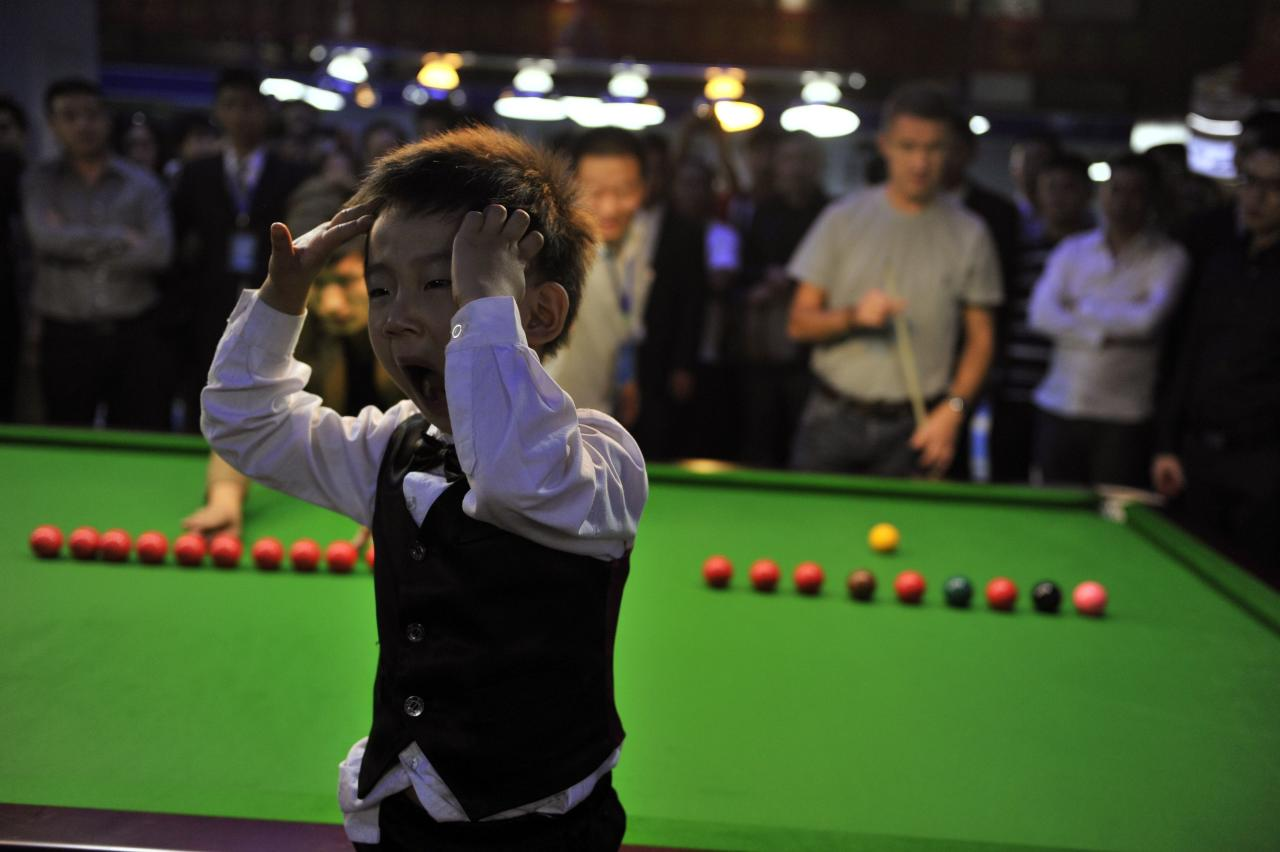 Three-year-old Wang Wuka yawns as he plays snooker with seven-time World Championship winner Stephen Hendry (back R, holding cue) of Britain in Beijing, September 22, 2013. Wuka's father Wang Yin, a snooker fan, has been teaching his son the sport for more than two years. The boy, who vows to be a top snooker player, undergoes five hours of training daily to shoot the balls with precision. Picture taken September 22, 2013. REUTERS/Stringer (CHINA - Tags: SPORT SOCIETY) CHINA OUT. NO COMMERCIAL OR EDITORIAL SALES IN CHINA