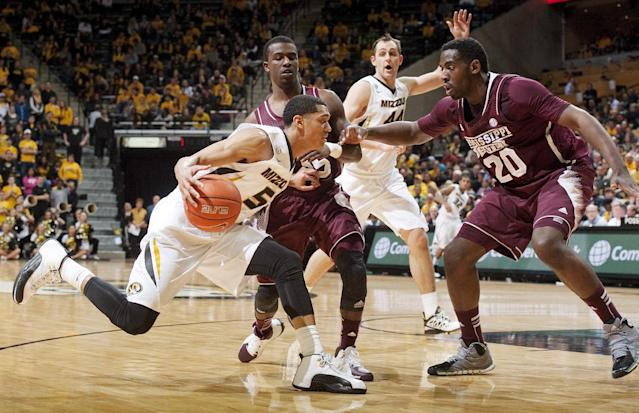 Missouri's Jordan Clarkson, left, tries to dribble past Mississippi State's Gavin Ware, right, and I.J. Ready as teammate Ryan Rosburg, back, calls for the ball during the first half of an NCAA college basketball game Saturday, March 1, 2014, in Columbia, Mo. (AP Photo/L.G. Patterson)
