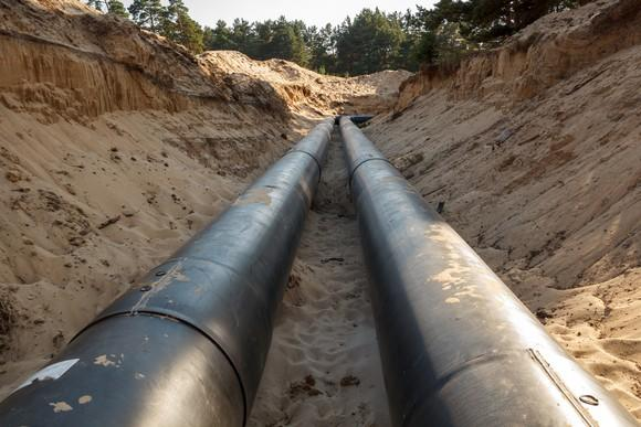 An uncovered pipeline under construction with sand around it.
