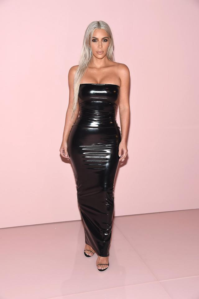 Kim Kardashian wears a skintight black patent leather dress at the Tom Ford SS18 runway show in New York. (Photo: Getty)