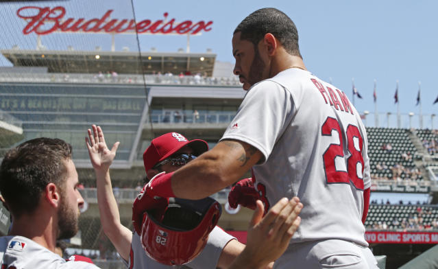 St. Louis Cardinals' Tommy Pham, right, is greeted in the dugout after he scored on a two-run single by Dexter Fowler off Minnesota Twins pitcher Lance Lynn in the first inning of a baseball game Wednesday, May 16, 2018, in Minneapolis. (AP Photo/Jim Mone)