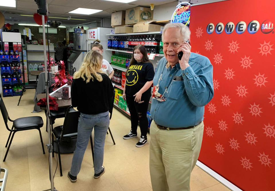 Store owner Richard Ravenscroft talks on a phone inside the Coney Market in Lonaconing Md., Thursday, Jan. 21, 2021, where a jackpot-winning Powerball ticket worth $731 million was sold this week. (Colin Campbell/The Baltimore Sun via AP)