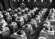 "<p>Elementary school students place their heads on their desk during the day's ""rest period.""</p>"