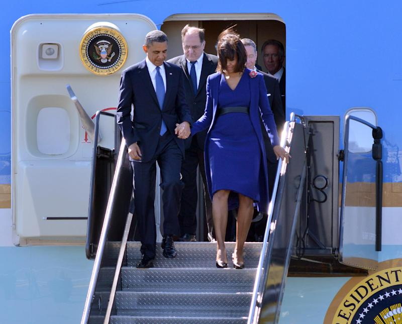 President Barack Obama  and first lady Michelle Obama depart Air Force One at Boston's Logan International Airport in Boston, Thursday, April 18, 2013, before attending an interfaith service for the victims of the bombings at the finish line of the Boston Marathon. Also seen is  Rep. Michael Capuano, D-Mass. is at center. (AP Photo/Josh Reynolds)
