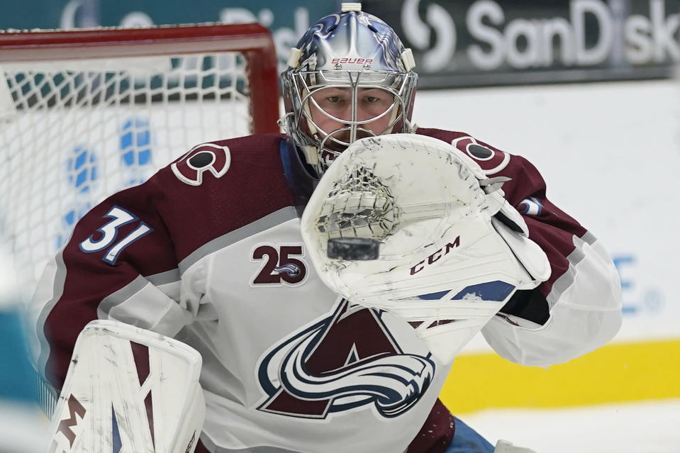 Colorado Avalanche goaltender Philipp Grubauer (31) catches a shot attempt by the San Jose Sharks during the second period of an NHL hockey game in San Jose, Calif., Monday, March 1, 2021. (AP Photo/Jeff Chiu)