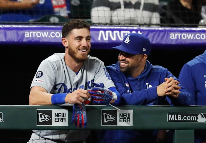Los Angeles Dodgers' Cody Bellinger smiles as he joins a teammate on the dugout rail after hitting a solo home run off Colorado Rockies relief pitcher Bryan Shaw in the eighth inning of a baseball game Sunday, April 7, 2019, in Denver. The Dodgers went on to win 12-6. (AP Photo/David Zalubowski)