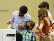 Liberal leader Justin Trudeau casts his ballot in the 44th general federal election as he's joined by his children, Xavier, Ella-Grace and Hadrien in Montreal on Monday, Sept. 20, 2021. (Sean Kilpatrick/The Canadian Press via AP)