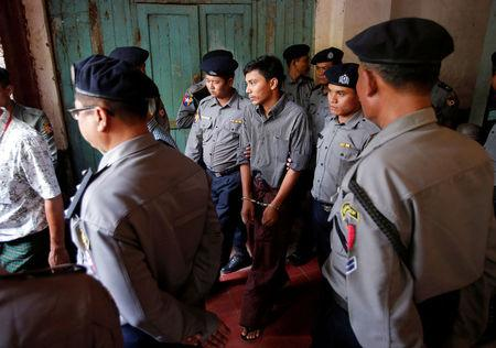 Detained Reuters journalist Kyaw Soe Oo is escorted by police after a court hearing in Yangon, Myanmar March 14, 2018. REUTERS/Stringer