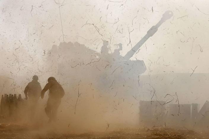 Israeli soldiers fire a howitzer amid smoke and flying debris