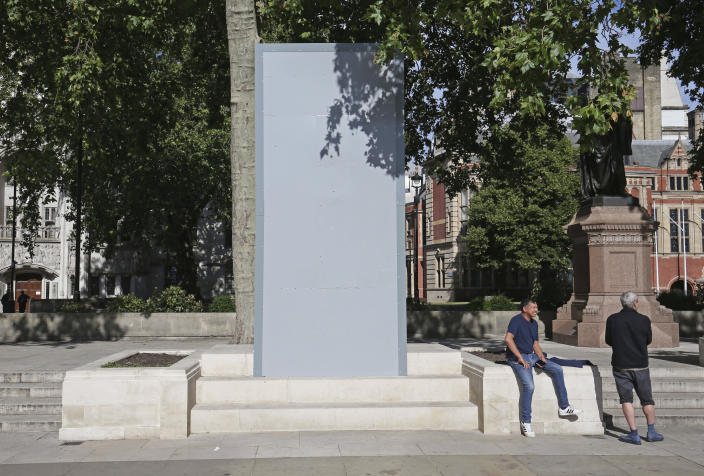 People next to a boarded up Mahatma Gandhi statue on Parliament Square in London, early Saturday June 13, 2020. Many monuments and statues have been boarded up to protect them from vandalism, having become a major focus of contention in demonstrations against racism and police violence following the death of George Floyd in the United States. (Jonathan Brady/PA via AP)